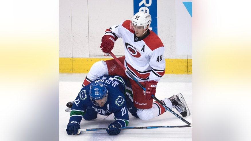 Carolina Hurricanes center Victor Rask (49) fights for control of the puck with Vancouver Canucks left wing Daniel Sedin (22) during the second period of an NHL hockey game in Vancouver, British Columbia, Sunday, Oct. 16, 2016. (Jonathan Hayward/The Canadian Press via AP)
