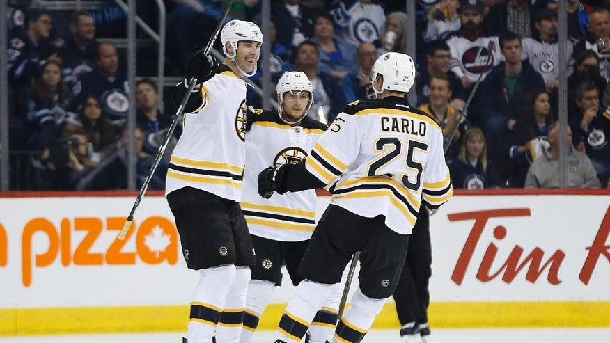 Boston Bruins' Zdeno Chara (33), Ryan Spooner (51) and Brandon Carlo (25) celebrates Chara's goal which was called back due to being offside during second period NHL hockey action in Winnipeg, Manitoba, Monday, Oct. 17, 2016. (John Woods/The Canadian Press via AP)