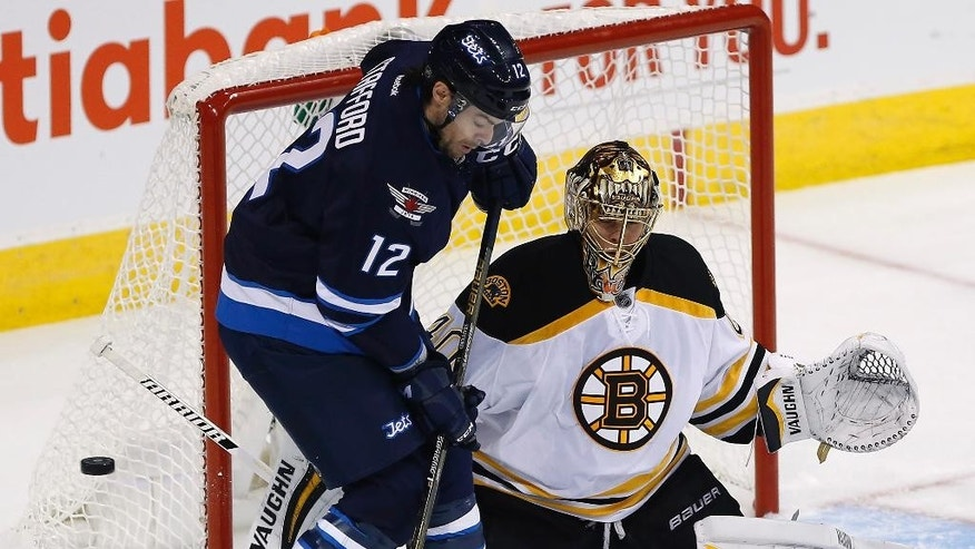Winnipeg Jets' Drew Stafford's (12) deflects the puck against Boston Bruins goaltender Tuukka Rask (40) during first period NHL action in Winnipeg, Manitoba, Monday, Oct. 17, 2016. (John Woods/The Canadian Press via AP)