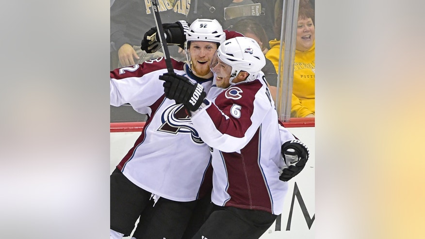 Colorado Avalanche defenseman Erik Johnson (6) congraulates Colorado Avalanche left wing Gabriel Landeskog (92) on his game winnging goal during the overtime period of an NHL hockey game against the Pittsburgh Penguins on Monday, Oct. 17, 2016, in Pittsburgh. The Avalanche defeated the Penguins 4-3. (AP Photo/Fred Vuich)