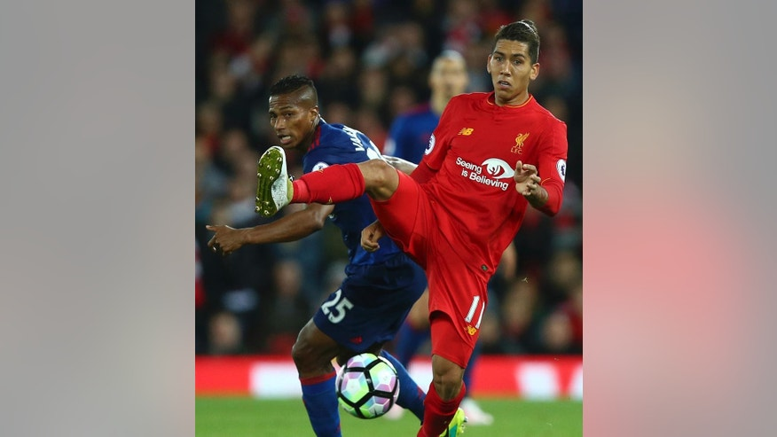 Liverpool's Roberto Firmino, right, challenges for the ball with Manchester United's Antonio Valencia during the English Premier League soccer match between Liverpool and Manchester United at Anfield stadium in Liverpool, England, Monday, Oct. 17, 2016. (AP Photo/Dave Thompson)