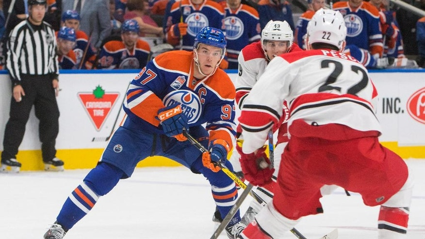 Edmonton Oilers' Connor McDavid (97) handles the puck in front of Carolina Hurricanes' Brett Pesce (22) as Victor Rask (49) watches during the second period of an NHL hockey game Tuesday, Oct. 18, 2016, in Edmonton, Alberta. (Amber Bracken/The Canadian Press via AP)