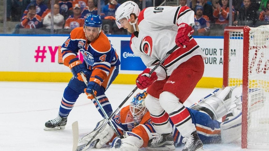 Carolina Hurricanes' Elias Lindholm (16) looks for the puck after being stopped by Edmonton Oilers goalie Cam Talbot (33) as Kris Russell (4) defends during the first period of an NHL hockey game Tuesday, Oct. 18, 2016, in Edmonton, Alberta. (Amber Bracken/The Canadian Press via AP)
