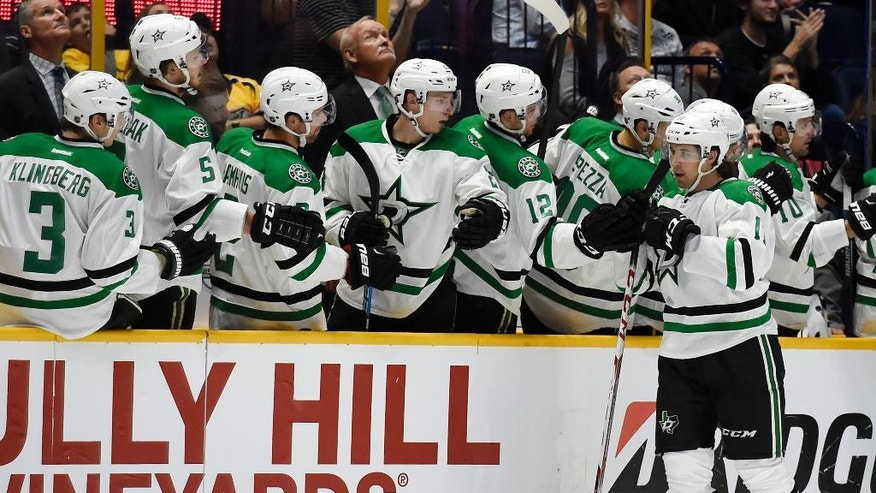 Dallas Stars left wing Curtis McKenzie (11) is congratulated after scoring a goal against the Nashville Predators during the second period of an NHL hockey game, Tuesday, Oct. 18, 2016, in Nashville, Tenn. (AP Photo/Mark Zaleski)