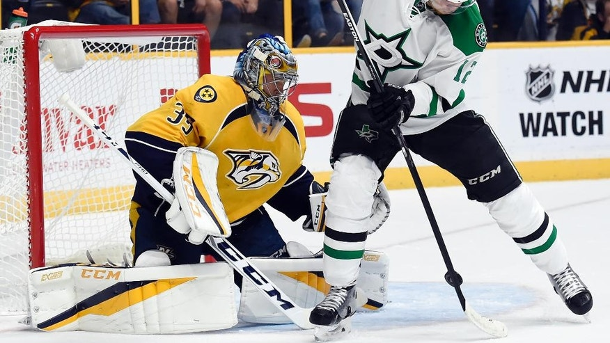Dallas Stars center Radek Faksa (12), of Czech Republic, tries to redirect a shot past Nashville Predators goalie Pekka Rinne (35), of Finland, during the first period of an NHL hockey game, Tuesday, Oct. 18, 2016, in Nashville, Tenn. (AP Photo/Mark Zaleski)