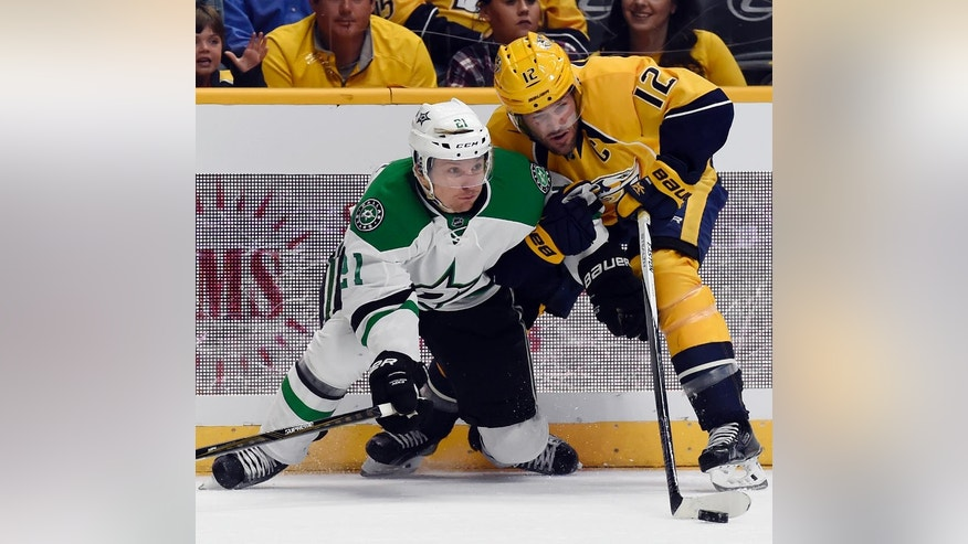Dallas Stars left wing Antoine Roussel (21), of France, works against Nashville Predators center Mike Fisher (12) for the puck during the first period of an NHL hockey game, Tuesday, Oct. 18, 2016, in Nashville, Tenn. (AP Photo/Mark Zaleski)