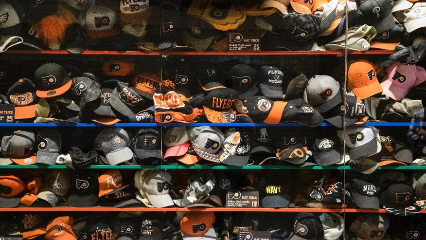 Philadelphia Flyers fans' hats, tossed on the ice after a player scored a hat trick, have been collected through the years and are displayed in a case at the Wells Fargo Center in Philadelphia, Wednesday, Oct. 19, 2016. The Flyers play their first home opener without founder Ed Snider on Thursday. Headed into 50 years of hockey in Philly, the Flyers hope to make this season memorable. (AP Photo/Matt Rourke)