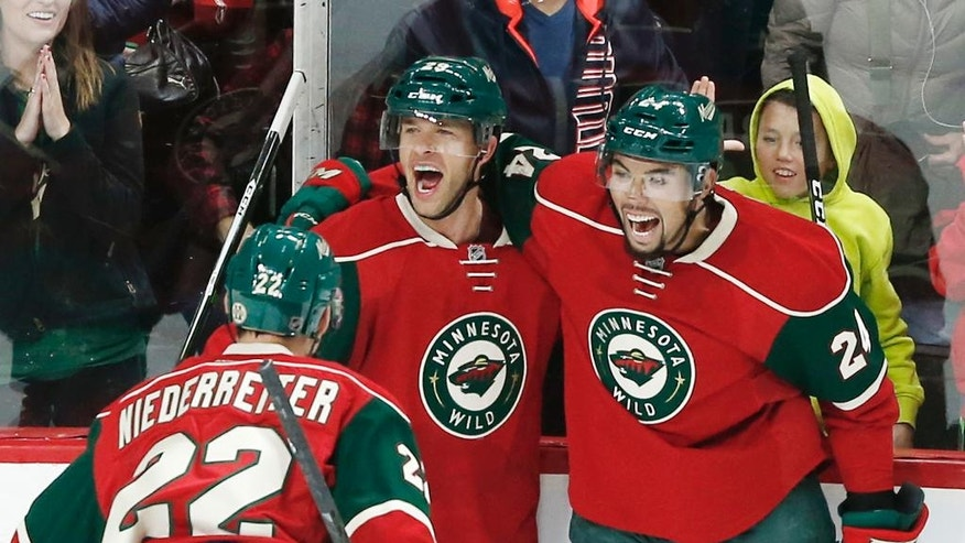 Minnesota Wild defenseman Matt Dumba, right, celebrates a goal by Jason Pominville, center, off Los Angeles Kings goalie Jeff Zatkoff in the first period of an NHL hockey game, Tuesday, Oct. 18, 2016, in St. Paul, Minn. (AP Photo/Jim Mone)