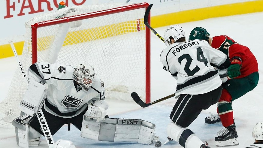 Los Angeles Kings goalie Jeff Zatkoff, left, stops a shot as Derek Forbort keeps Minnesota Wild's Teemu Pulkkinen, right, away from a rebound in the first period of an NHL hockey game, Tuesday, Oct. 18, 2016, in St. Paul, Minn. (AP Photo/Jim Mone)