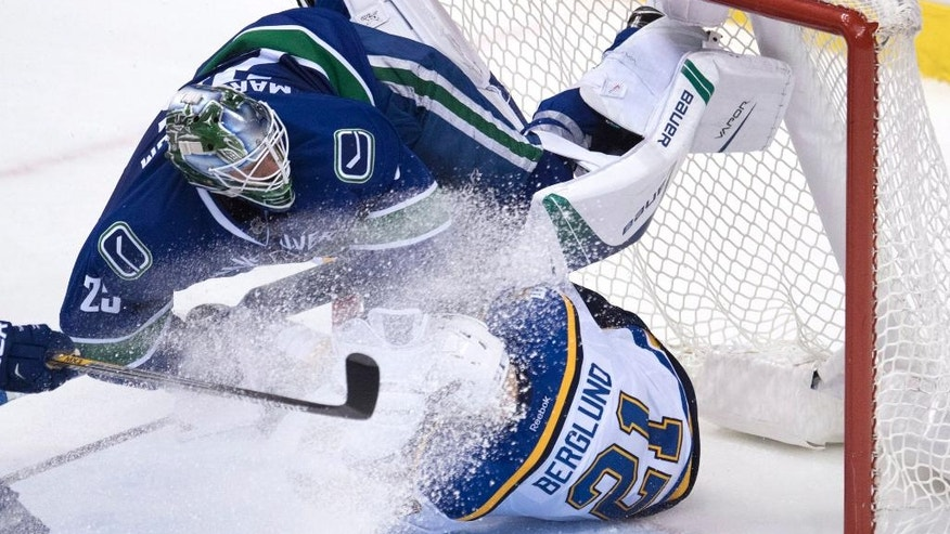 Vancouver Canucks goalie Jacob Markstrom (25) gets taken out by St. Louis Blues center Patrik Berglund (21) during the third period of an NHL hockey game Tuesday, Oct. 18, 2016, in Vancouver, British Columbia. (Jonathan Hayward/The Canadian Press via AP)