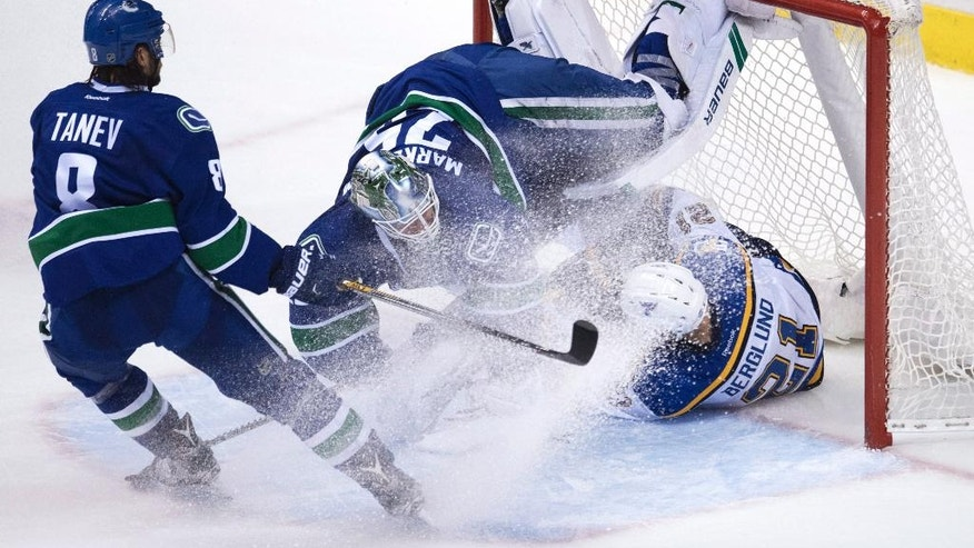 Vancouver Canucks goalie Jacob Markstrom (25) gets taken out by St. Louis Blues centre Patrik Berglund (21) as Canucks defenseman Christopher Tanev (8) stops in front of the goal during the third period of an NHL hockey game Tuesday, Oct. 18, 2016, in Vancouver, British Columbia. (Jonathan Hayward/The Canadian Press via AP)