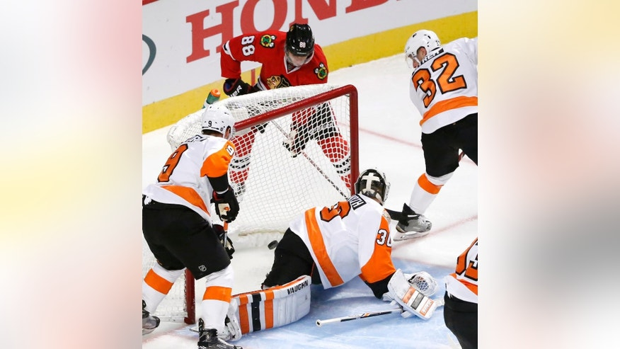 Chicago Blackhawks' Patrick Kane (88) scores past Philadelphia Flyers goalie Michal Neuvirth (30) as Ivan Provorov (9) and Mark Streit watch during the first period of an NHL hockey game Tuesday, Oct. 18, 2016, in Chicago. (AP Photo/Charles Rex Arbogast)