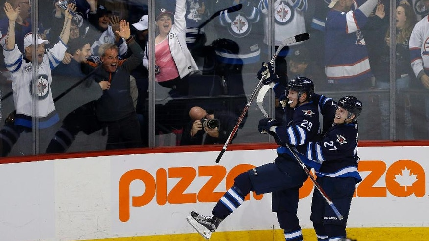 Winnipeg Jets' Nikolaj Ehlers (27) and Patrik Laine (29) celebrate Laine's overtime goal against the Toronto Maple Leafs in an NHL hockey game Wednesday, Oct. 19, 2016, in Winnipeg, Manitoba. (John Woods/The Canadian Press via AP)