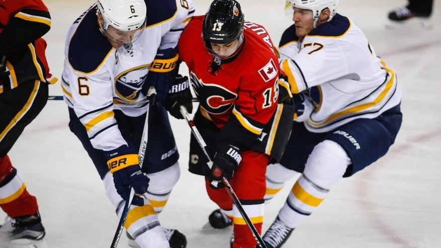 Buffalo Sabres' Cody Franson, left, and Dmitry Kulikov, right, from Russia, sandwich Calgary Flames' Johnny Gaudreau during the first period of an NHL hockey game Tuesday, Oct. 18, 2016, in Calgary, Alberta. (Jeff McIntosh/The Canadian Press via AP)