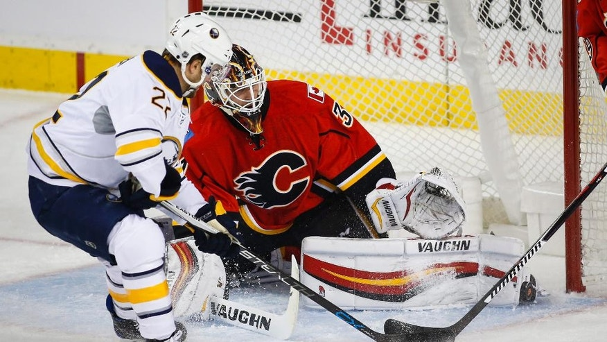 Buffalo Sabres' Johan Larsson, left, from Sweden, tries to get the puck past Calgary Flames goalie Chad Johnson during the first period of an NHL hockey game Tuesday, Oct. 18, 2016, in Calgary, Alberta. (Jeff McIntosh/The Canadian Press via AP)