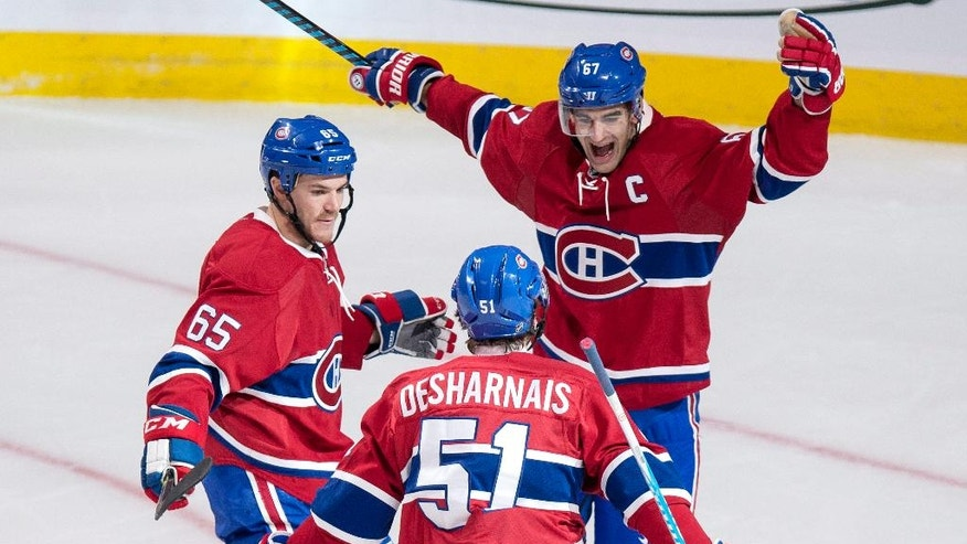 Montreal Canadiens' David Desharnais celebrates his goal against the Pittsburgh Penguins with teammates Max Pacioretty, right, and Andrew Shaw during second period NHL hockey action, Tuesday, Oct. 18, 2016 in Montreal. (Paul Chiasson/The Canadian Press via AP)