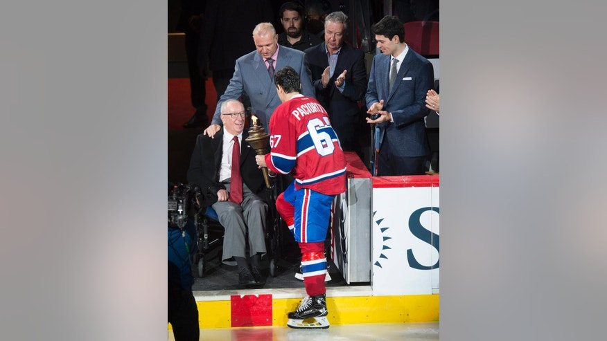Montreal Canadiens captain Max Pacioretty is presented with the flame from Senator Jacques Demers during a torch ceremony for the NHL hockey team's home-opener, against the Pittsburgh Penguins on Tuesday, Oct. 18, 2016, in Montreal. Looking on are Canadiens coach Michel Therrien, back left, and inured goaltender Carey Price, right,. (Paul Chiasson/The Canadian Press via AP)