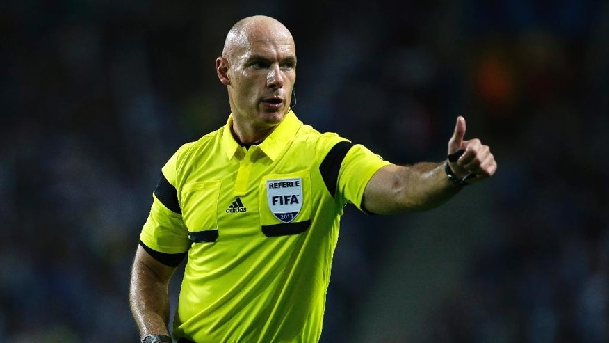 FILE - In this Tuesday, Oct. 1, 2013 file photo, referee Howard Webb gestures during the Champions League group G soccer match between FC Porto and Atletico de Madrid in Porto, northern Portugal. Moments before the start of the most game of his life, Webb had been struck down by another bout of Obsessive compulsive disorder, a condition in which a person has obsessive thoughts and compulsive behavior. Webb kept the condition secret throughout a career that saw him referee the Champions League final and World Cup final in the same year, 2010, fearing the harsh world of soccer would mark him down as mentally unsound. (AP Photo/Armando Franca, file)