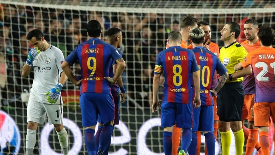 Manchester City's goalkeeper Claudio Bravo, left, leaves the pitch after being shown a red card for handling the ball outside the box during a Champions League, Group C soccer match between Barcelona and Manchester City, at the Camp Nou stadium in Barcelona, Wednesday, Oct. 19, 2016. (AP Photo/Manu Fernandez)
