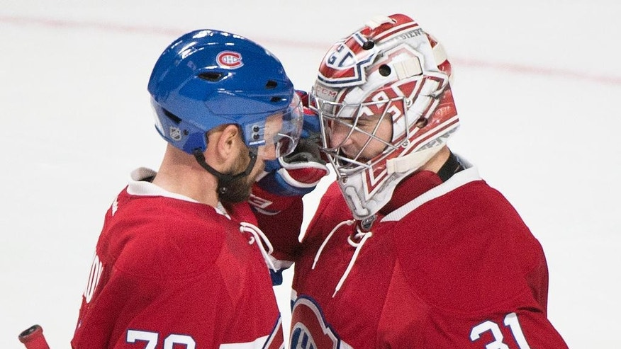 Montreal Canadiens goaltender Carey Price celebrates with teammate Andrei Markov (79) following their win over the Arizona Coyotes in an NHL hockey game, Thursday, Oct. 20, 2016 in Montreal. (Graham Hughes/The Canadian Press via AP)