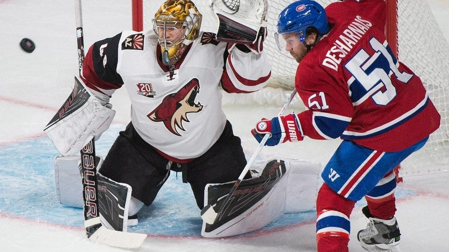 Arizona Coyotes goaltender Justin Peters attempts a save as Montreal Canadiens' David Desharnais looks for a rebound during the second period of an NHL hockey game, Thursday, Oct. 20, 2016 in Montreal. (Graham Hughes/The Canadian Press via AP)