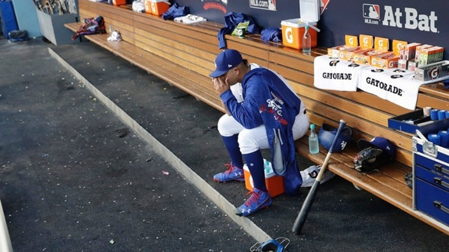 Los Angeles Dodgers' Julio Urias sits in the dugout during the second inning of Game 4 of the National League baseball championship series against the Chicago Cubs Wednesday, Oct. 19, 2016, in Los Angeles. (AP Photo/David J. Phillip)