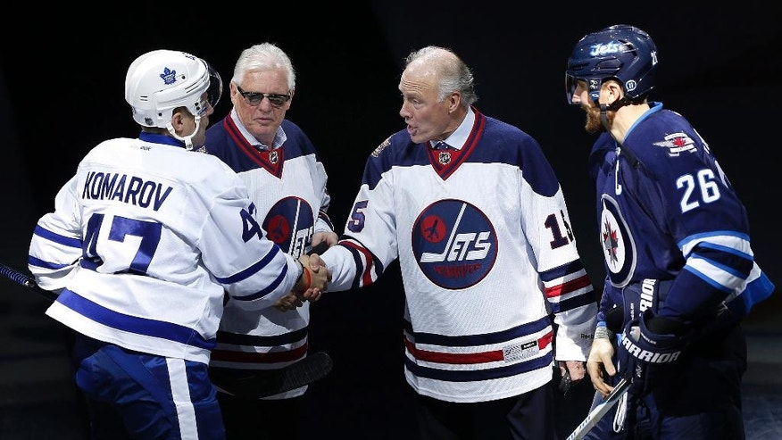 Former Winnipeg Jets' Anders Hedberg, second from right, shakes hands with Toronto Maple Leafs' Leo Komarov (47) as Ulf Nilsson and Winnipeg Jets' Blake Wheeler (26) watch during the induction ceremony for the Winnipeg Jets Hall of Fame in Winnipeg, Manitoba, on Wednesday, Oct. 19, 2016. Bobby Hull was also inducted but did not attend. (John Woods/The Canadian Press via AP)