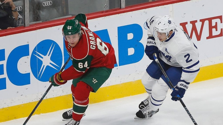 Minnesota Wild's Mikael Granlund controls the puck against Toronto Maple Leafs' Matt Hunwick in the first period of an NHL hockey game Thursday, Oct. 20, 2016, in St. Paul, Minn. (AP Photo/Stacy Bengs)
