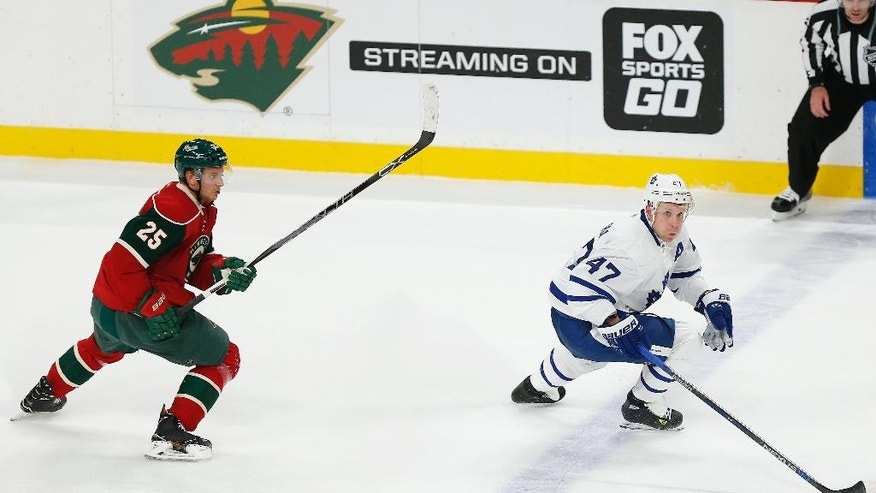 Toronto Maple Leafs' Leo Komarov controls the puck against Minnesota Wild's Jonas Brodin in the second period of an NHL hockey game Thursday, Oct. 20, 2016, in St. Paul, Minn. (AP Photo/Stacy Bengs)
