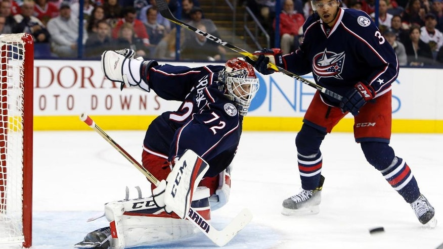 Columbus Blue Jackets' Sergei Bobrovsky, left, of Russia, makes a save against the Chicago Blackhawks as teammate Seth Jones looks for the rebound during the third period of an NHL hockey game Friday, Oct. 21, 2016, in Columbus, Ohio. (AP Photo/Jay LaPrete)