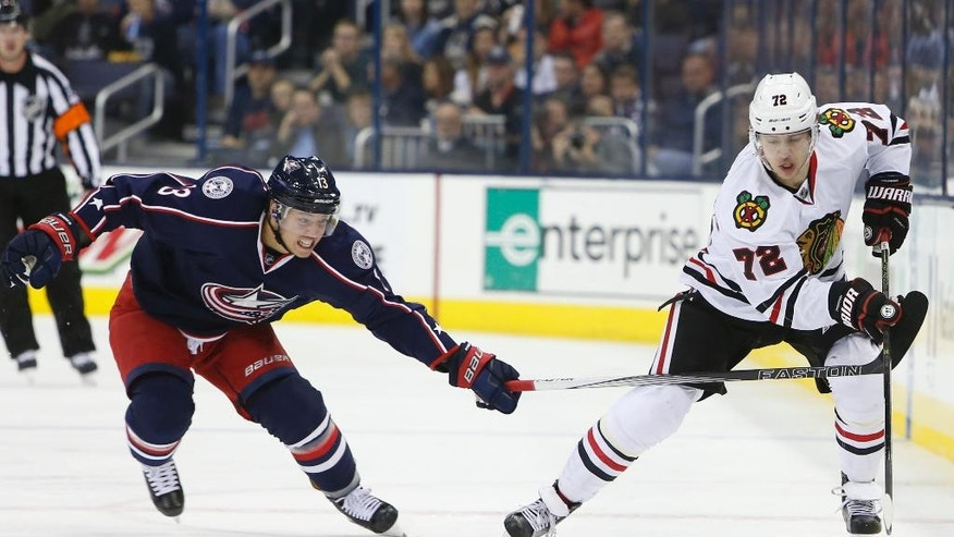 Chicago Blackhawks' Artemi Panarin, right, of Russia, carries the puck across the blue line as Columbus Blue Jackets' Cam Atkinson defends during the first period of an NHL hockey game Friday, Oct. 21, 2016, in Columbus, Ohio. (AP Photo/Jay LaPrete)