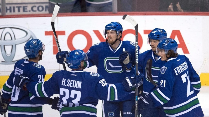 Vancouver Canucks left wing Daniel Sedin (22) celebrates his goal against the Buffalo Sabres with teammates Brandon Sutter (20), Henrick Sedin (33), Philip Larsen (63) and Loui Eriksson (21) during the third period of an NHL hockey game Thursday, Oct. 20, 2016, in Vancouver, British Columbia. (Jonathan Hayward/The Canadian Press via AP)