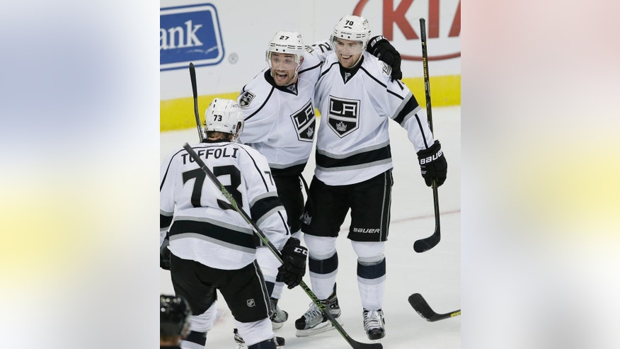 Los Angeles Kings defenseman Alec Martinez (27) celebrates after scoring an overtime goal with teammates Tanner Pearson (70) and Tyler Toffoli (73) during an NHL hockey game against the Dallas Stars, Thursday, Oct. 20, 2016, in Dallas. (AP Photo/LM Otero)