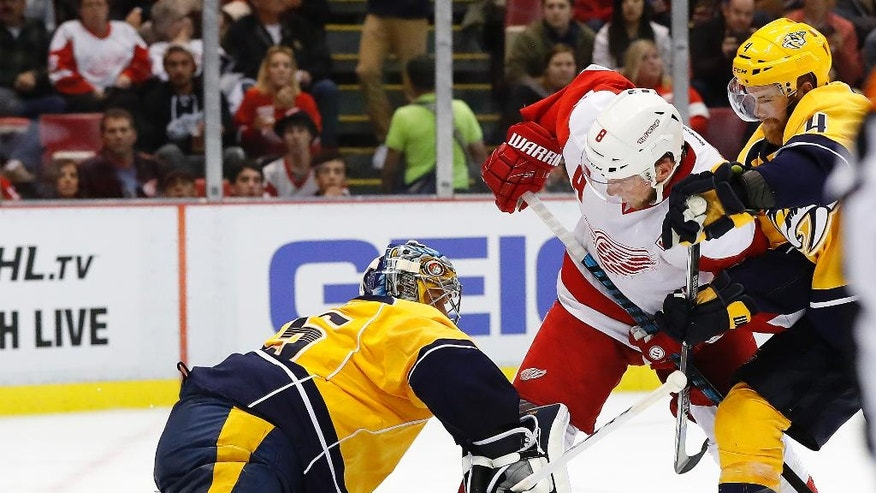 Detroit Red Wings left wing Justin Abdelkader (8) scores on Nashville Predators goalie Pekka Rinne, left, as Ryan Ellis (4) defends during the second period of an NHL hockey game Friday, Oct. 21, 2016, in Detroit. (AP Photo/Paul Sancya)