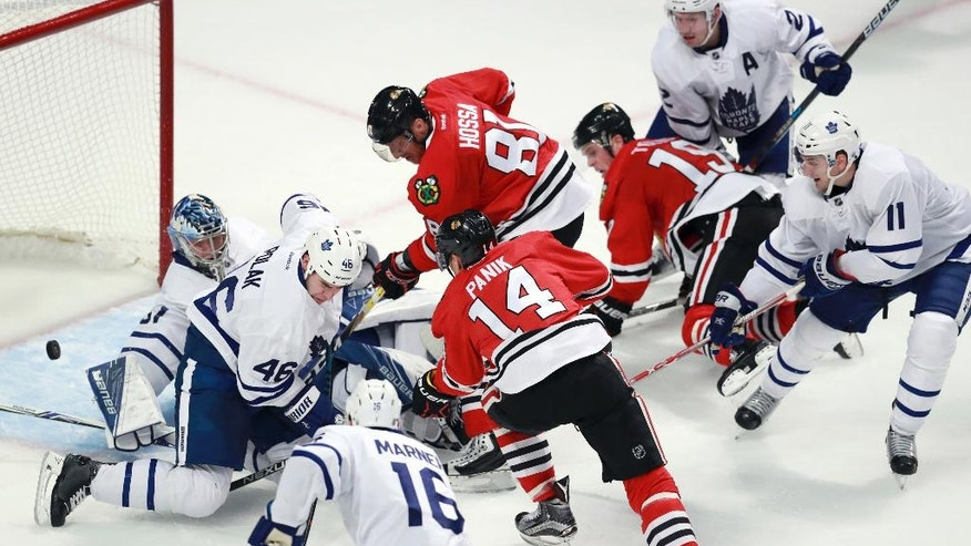 Chicago Blackhawks left wing Richard Panik (14) pokes a goal past Toronto Maple Leafs goalie Frederik Andersen (31) during the third period of an NHL hockey game Saturday, Oct. 22, 2016, in Chicago. (AP Photo/Jeff Haynes)