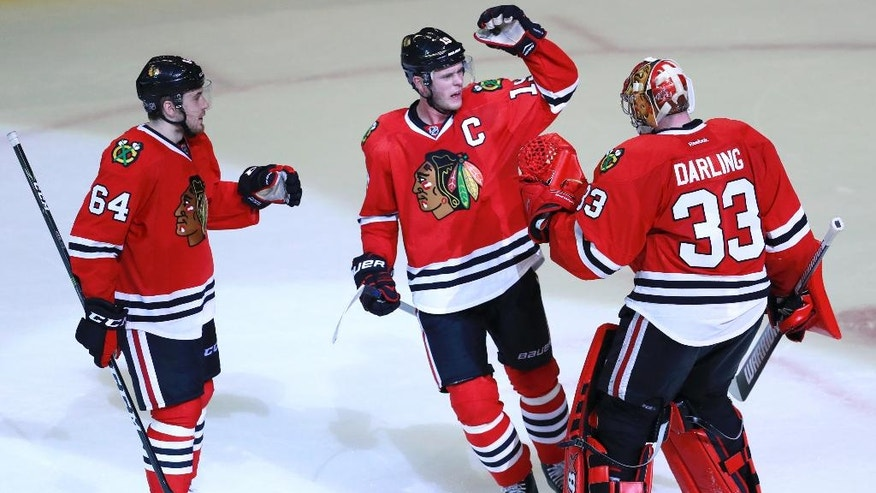 Chicago Blackhawks center Jonathan Toews, center, and left wing Tyler Motte (64) celebrate with goalie Scott Darling (33) after they won in an overtime shootout against the Toronto Maple Leafs. (AP Photo/Jeff Haynes)