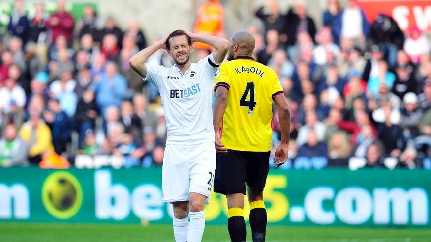 Swansea City's Gylfi Sigurdsson, left, walks past Watford's Younes Kaboul during the English Premier League soccer match at the Liberty Stadium, Swansea, Wales, Saturday, Oct. 22, 2016. (Simon Galloway/PA via AP)