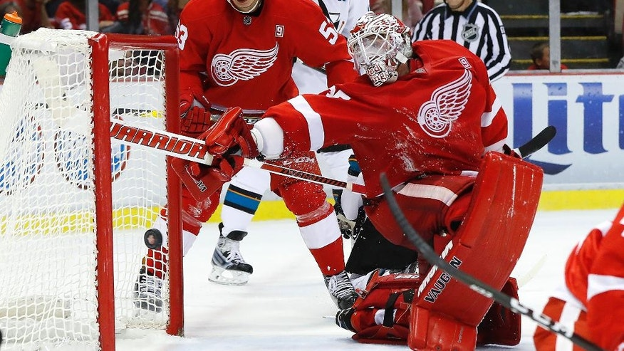 Detroit Red Wings goalie Jimmy Howard (35) reaches back to block a San Jose Sharks shot at the end of the second period of an NHL hockey game in Detroit, Saturday, Oct. 22, 2016. (AP Photo/Paul Sancya)