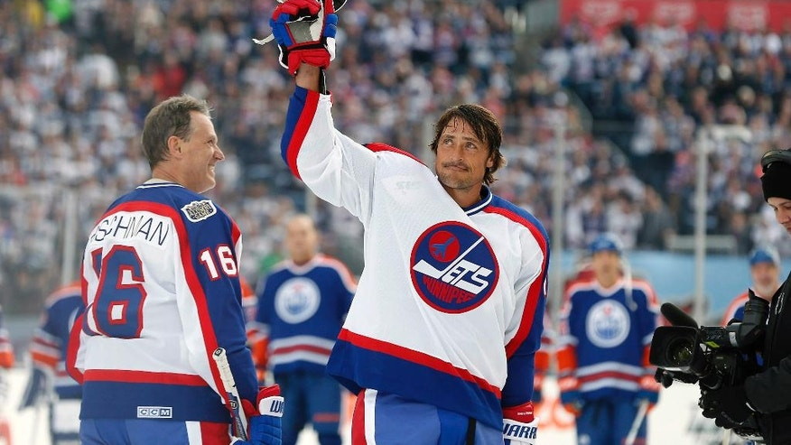 Former Winnipeg Jets player Teemu Selanne (13) waves to the crowd at Investors Group Field prior to the NHL Heritage Classic Alumni hockey game in Winnipeg, Manitoba, Saturday, Oct. 22, 2016. (John Woods/The Canadian Press via AP)