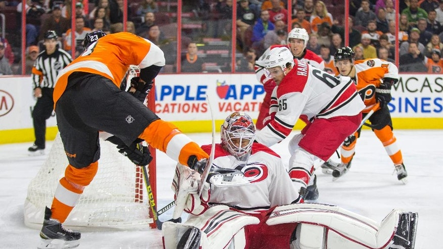 Carolina Hurricanes' Eddie Lack, center, tries to stop Philadelphia Flyers' Brandon Manning, left, before Manning eventually scored, as Hurricanes' Ron Hainsey, right, tries to come over to help during the second period of an NHL hockey game, Saturday, Oct. 22, 2016, in Philadelphia. (AP Photo/Chris Szagola)