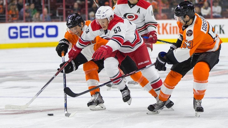 Carolina Hurricanes' Jeff Skinner, center, goes after the puck as he tries to split between Philadelphia Flyers' Brayden Schenn, left, and Shayne Gostisbehere, right, during the first period of an NHL hockey game, Saturday, Oct. 22, 2016, in Philadelphia. (AP Photo/Chris Szagola)