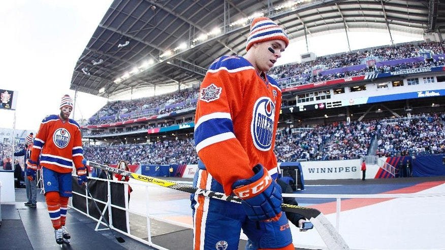 Edmonton Oilers' Connor McDavid (97) and Eric Gryba (62) leave the ice after the warmup skate at the NHL Heritage Classic in Winnipeg, Manitoba, Sunday, Oct. 23, 2016. (John Woods/The Canadian Press via AP)