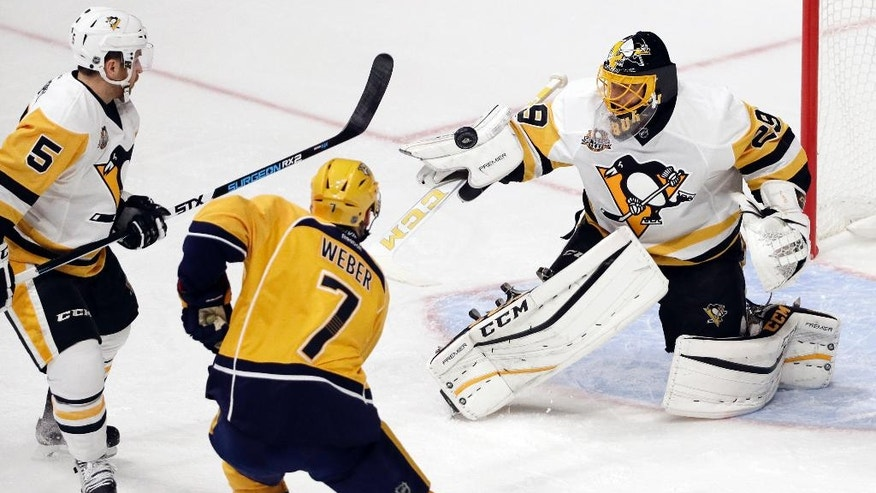 Pittsburgh Penguins goalie Marc-Andre Fleury (29) blocks a shot as defenseman David Warsofsky (5) and Nashville Predators defenseman Yannick Weber (7), of Switzerland, watch for the rebound during the first period of an NHL hockey preseason game Saturday, Oct. 22, 2016, in Nashville, Tenn. (AP Photo/Mark Humphrey)