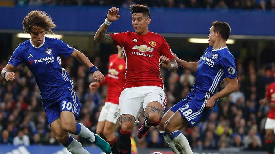 Manchester United's Marcos Rojo, center, Chelsea's David Luiz, left, and Chelsea's Cesar Azpilicueta challenge for the ball during the English Premier League soccer match between Chelsea and Manchester United at Stamford Bridge stadium in London, Sunday, Oct. 23, 2016.(AP Photo/Kirsty Wigglesworth)