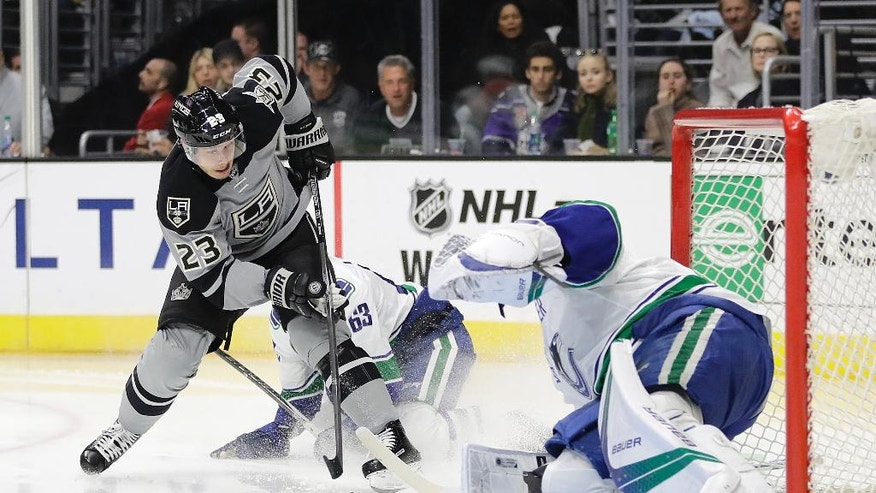 Los Angeles Kings' Dustin Brown, left, shoots and scores against Vancouver Canucks goalie Jacob Markstrom, of Sweden, during the second period of an NHL hockey game Saturday, Oct. 22, 2016, in Los Angeles. (AP Photo/Jae C. Hong)