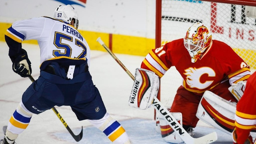 St. Louis Blues' David Perron, left, scores on Calgary Flames goalie Chad Johnson during the third period of an NHL hockey game against the Calgary Flames in Calgary, Alberta, Saturday, Oct. 22, 2016. (Jeff McIntosh/The Canadian Press via AP)