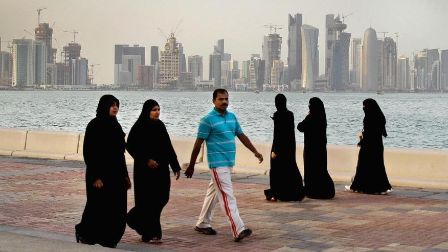 "FILE- In this Saturday, April 7, 2012 file photo, the new high-rise buildings of downtown Doha, photographed in the background as Qatari women and a man walk by the sea in Doha, Qatar. A worker on a Qatar World Cup stadium site has died in the first work-related fatality to be announced by organizers of the 2022 soccer tournament which has been dogged by concerns about labor conditions. Qatar has previously reported three deaths at stadium construction sites but said they were not ""work-related."" (AP Photo/Kamran Jebreili, File)"