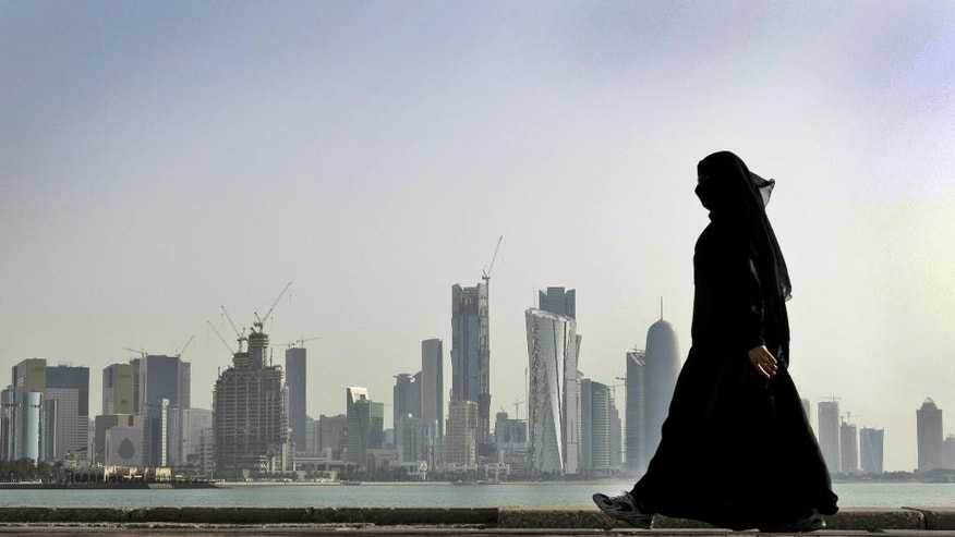 "FILE- In this May 14, 2010 file photo, a Qatari woman walks in front of the city skyline in Doha, Qatar. A worker on a Qatar World Cup stadium site has died in the first work-related fatality to be announced by organizers of the 2022 soccer tournament which has been dogged by concerns about labor conditions. Qatar has previously reported three deaths at stadium construction sites but said they were not ""work-related.""  (AP Photo/Kamran Jebreili, File)"