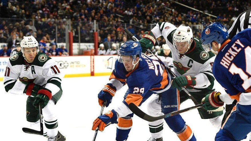 New York Islanders left wing Brock Nelson (29) and defenseman Thomas Hickey (14) battle for the puck against Minnesota Wild left wing Zach Parise (11) and center Mikko Koivu (9) in the first period of an NHL hockey game in New York, Sunday, Oct. 23, 2016. (AP Photo/Kathy Kmonicek)