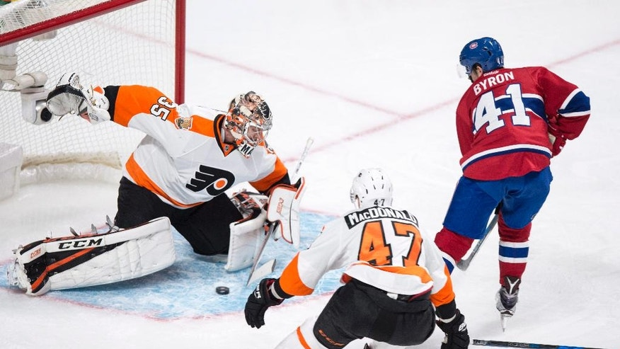 Philadelphia Flyers goalie Steve Mason makes a save off Montreal Canadiens' Paul Byron (41) as defenceman Andrew MacDonald (47) looks on during first period NHL hockey action in Montreal on Monday, Oct. 24, 2016. (Paul Chiasson/The Canadian Press via AP)